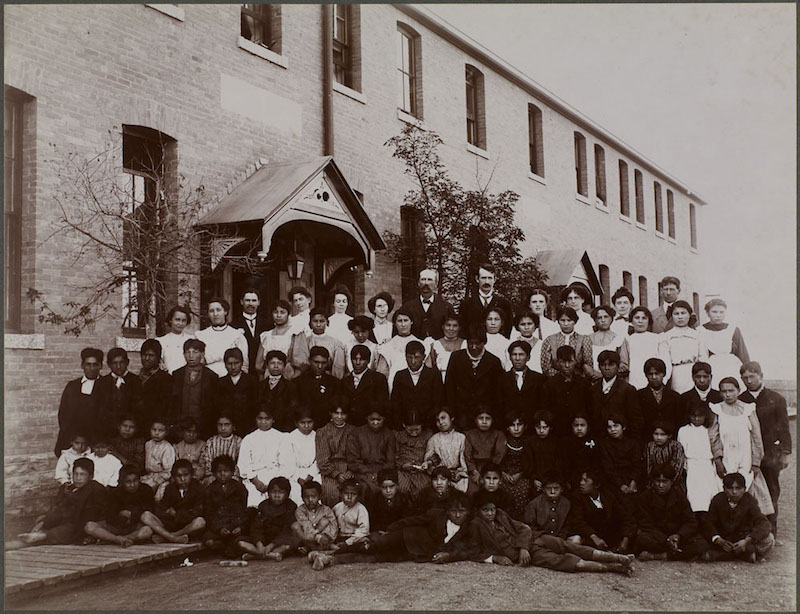 Kinderen en staf poserend voor hun Indian Residential School in Regina, Saskatchewan