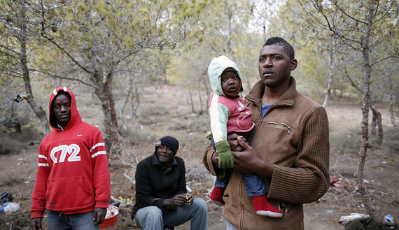 African migrants stand in a clandestine campsite named Bolingo in woods in northern Morocco near the border fence with Spain's north African enclave Melilla